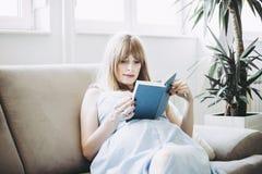 Βιβλίο ανάγνωσης εγκύων γυναικών στο διαμέρισμα στοκ εικόνα με δικαίωμα ελεύθερης χρήσης