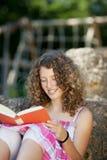 Βιβλίο ανάγνωσης κοριτσιών κλίνοντας στο βράχο Στοκ φωτογραφία με δικαίωμα ελεύθερης χρήσης