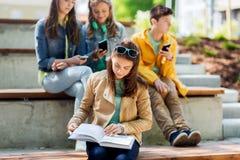 Βιβλίο ανάγνωσης κοριτσιών σπουδαστών γυμνασίου υπαίθρια στοκ φωτογραφίες