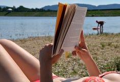 Βιβλίο ανάγνωσης κοριτσιών στην παραλία Στοκ Φωτογραφίες