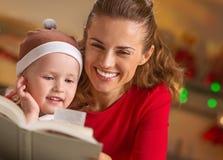 Βιβλίο ανάγνωσης μητέρων και μωρών διακοσμημένη στη Χριστούγεννα κουζίνα Στοκ Εικόνες