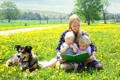 Βιβλίο ανάγνωσης μητέρων στα παιδιά έξω Στοκ Εικόνες