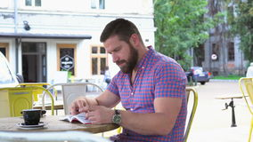 Βιβλίο ανάγνωσης νεαρών άνδρων στον καφέ, ολισθαίνων ρυθμιστής που βλασταίνεται αριστερά απόθεμα βίντεο