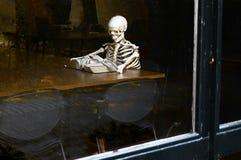 Βιβλίο ανάγνωσης σκελετών στη βιβλιοθήκη Στοκ Φωτογραφία