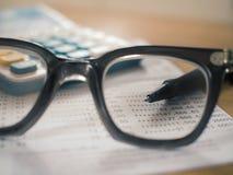 Βιβλίο απολογισμού αποταμίευσης με τη μάνδρα που στρέφεται eyeglasses στους φακούς στοκ εικόνα