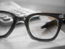 Βιβλίο απολογισμού αποταμίευσης με τη μάνδρα που στρέφεται eyeglasses στους φακούς στοκ εικόνες