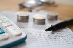 Βιβλίο απολογισμού αποταμίευσης με τη μάνδρα, τον υπολογιστή και το νόμισμα στοκ φωτογραφίες