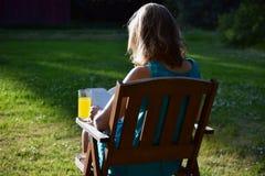 Βιβλίο γυναικών readin στον κήπο στοκ εικόνα