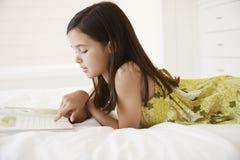 Βιβλίο ιστορίας ανάγνωσης κοριτσιών στο κρεβάτι στοκ εικόνα