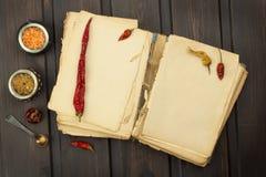 Βιβλίο και λαχανικά συνταγής Πιπέρι και ντομάτες τσίλι Προετοιμασία τροφίμων σύμφωνα με το παλαιό βιβλίο συνταγής Στοκ φωτογραφία με δικαίωμα ελεύθερης χρήσης