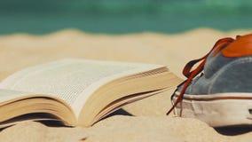 Βιβλίο και παπούτσια σε μια άμμο παραλιών φιλμ μικρού μήκους