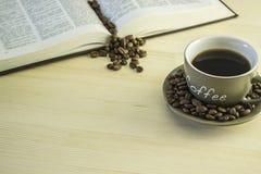 Βιβλίο και φλιτζάνι του καφέ στον ξύλινο πίνακα Στοκ εικόνα με δικαίωμα ελεύθερης χρήσης