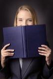 Βιβλίο κοντά στο πρόσωπό της Στοκ Φωτογραφίες