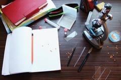 Βιβλίο, σημειωματάρια, στυλός, μολύβι και μικροσκόπιο στον πίνακα Στοκ φωτογραφία με δικαίωμα ελεύθερης χρήσης