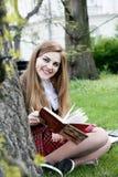 Βιβλίο/σπουδαστής ανάγνωσης κοριτσιών που διαβάζει ένα βιβλίο στο πάρκο/ Στοκ Εικόνα