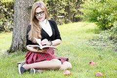 Βιβλίο/σπουδαστής ανάγνωσης κοριτσιών που διαβάζει ένα βιβλίο στο πάρκο/ Στοκ Εικόνες