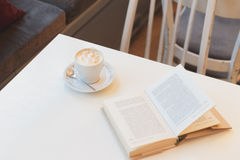 Βιβλίο στον άσπρο πίνακα με το φλιτζάνι του καφέ στον καφέ Στοκ Εικόνα