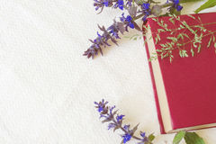 Βιβλίο του κόκκινου χρώματος στα λουλούδια τομέων σε έναν άσπρο ιστό Στοκ εικόνα με δικαίωμα ελεύθερης χρήσης