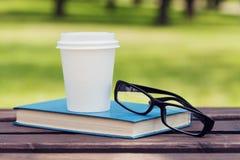 Βιβλίο, eyeglasses και φλυτζάνι εγγράφου με τον καφέ σε έναν πάγκο στο πάρκο σε μια ηλιόλουστη ημέρα, που διαβάζει το καλοκαίρι,  Στοκ εικόνες με δικαίωμα ελεύθερης χρήσης