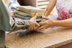 Βιβλιοθηκάριος που παίρνει τα βιβλία από το αγόρι στο μετρητή βιβλιοθήκης στοκ εικόνα με δικαίωμα ελεύθερης χρήσης