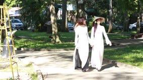 Βιετναμέζικα κορίτσια που φορούν το κωνικό καπέλο και AO Dai (βιετναμέζικο παραδοσιακό κοστούμι ή μακρύ φόρεμα) απόθεμα βίντεο