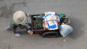 Βιετναμέζικη γυναίκα που ωθεί ένα σύνολο κάρρων των ανακυκλώσιμων αποβλήτων στοκ εικόνα