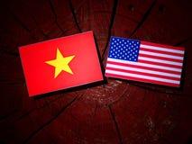 Βιετναμέζικη σημαία με την ΑΜΕΡΙΚΑΝΙΚΗ σημαία σε ένα κολόβωμα δέντρων στοκ εικόνες