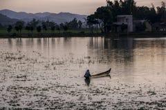 Βιετναμέζικος ψαράς στο ηλιοβασίλεμα που πλέει με μια βάρκα κατά μήκος της ακτής στοκ εικόνα με δικαίωμα ελεύθερης χρήσης