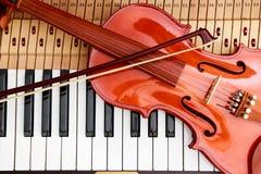 Βιολί και τόξο βιολιών στο υπόβαθρο κλειδιών πιάνων Στοκ Εικόνα