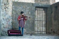 Βιολί παιχνιδιού γυναικών στην οδό στις μεσαιωνικές οχυρώσεις στοκ φωτογραφία