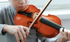 βιολί παιχνιδιού Unrecognizable χρονών αγόρι επτά που παίζει την κινηματογράφηση σε πρώτο πλάνο βιολιών Μπροστινή όψη Στοκ εικόνα με δικαίωμα ελεύθερης χρήσης
