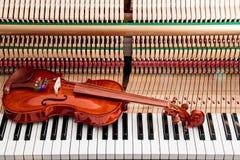 Βιολί στα γραπτά κλειδιά πιάνων με μέσα στο υπόβαθρο πιάνων Στοκ Εικόνες