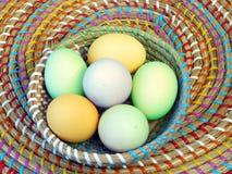 Βιολογικά οργανικά γαλαζοπράσινα κίτρινα τυρκουάζ αυγά Πάσχας σε ένα ζωηρόχρωμο καλάθι σε έναν ξύλινο πίνακα στοκ φωτογραφίες