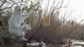 Βιολογικός κίνδυνος στη φύση, hazmat ερευνητής στο προστατευτικό κοστούμι που παίρνει τη μολυσμένη δειγματοληψία ύδατος στους σωλ απόθεμα βίντεο