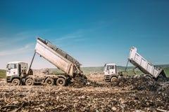 Βιομηχανικά βαρέων καθηκόντων φορτηγά εκφορτωτών που ξεφορτώνουν στο εργοτάξιο οικοδομής στοκ φωτογραφίες
