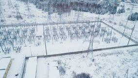 Βιομηχανικά κτήρια και μονωτές στο έδαφος σταθμών που καλύπτεται με το χιόνι απόθεμα βίντεο