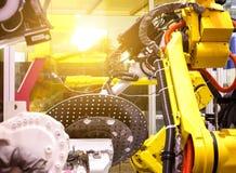 Βιομηχανικά ρομπότ στα βιομηχανικά ρομπότ εργοστασίων κατασκευαστών γραμμών παραγωγής στην κίνηση βάθος της θαμπάδας τομέων Στοκ Εικόνες