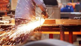 Βιομηχανικές εγκαταστάσεις κατασκευής Ένα άτομο που χρησιμοποιεί μια αλέθοντας μηχανή Λείανση της λεπτομέρειας Σπινθηρίσματα πυρκ απόθεμα βίντεο