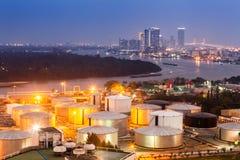 Βιομηχανικές δεξαμενές πετρελαίου σε εγκαταστάσεις καθαρισμού με την οικοδόμηση της εικονικής παράστασης πόλης Στοκ Φωτογραφία
