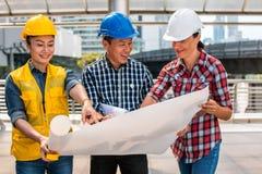 Βιομηχανική εφαρμοσμένη μηχανική κρανών ασφάλειας ένδυσης μηχανικών τρία που λειτουργεί και που μιλά με την επιθεώρηση σχεδίων να στοκ εικόνα με δικαίωμα ελεύθερης χρήσης