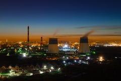 Βιομηχανική ζώνη της πόλης το βράδυ Σωλήνας λεβήτων, ηλιοβασίλεμα, φω'τα νύχτας Στοκ Φωτογραφίες