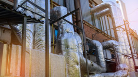 Βιομηχανική ζώνη, τοίχος του βιομηχανικού κτηρίου με τους σωλήνες Στοκ Φωτογραφίες