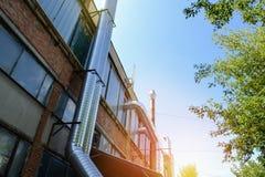Βιομηχανική ζώνη, τοίχος του βιομηχανικού κτηρίου με τους σωλήνες Στοκ Εικόνες