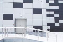 Βιομηχανική σύγχρονη πρόσοψη αποθηκών εμπορευμάτων με την πόρτα και τα βήματα Στοκ εικόνα με δικαίωμα ελεύθερης χρήσης