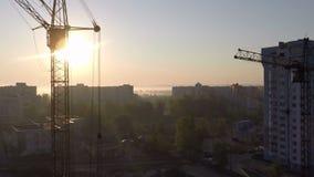 Βιομηχανικοί γερανοί κατασκευής και σκιαγραφίες οικοδόμησης πέρα από τον ήλιο στην ανατολή απόθεμα βίντεο