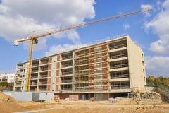 Βιομηχανικοί γερανοί πύργων στο εργοτάξιο οικοδομής, ατελές κτήριο Στοκ φωτογραφία με δικαίωμα ελεύθερης χρήσης