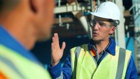 Βιομηχανικοί μηχανικός και εργαζόμενος που συζητούν στο εργοστάσιο Κινηματογράφηση σε πρώτο πλάνο απόθεμα βίντεο