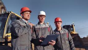 Βιομηχανικός άνδρας εργαζόμενος που εργάζεται στην ομάδα στον υπαίθριο μέσο πυροβολισμό εργοτάξιων οικοδομής φιλμ μικρού μήκους