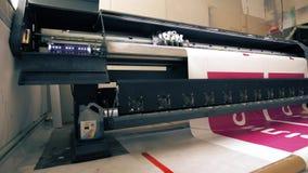 Βιομηχανικός εκτυπωτής που κάνει το μεγάλο ζωηρόχρωμο έμβλημα στο εργαστήριο φιλμ μικρού μήκους