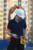 Βιομηχανικός εργάτης με τον εξοπλισμό ασφάλειας και χέρι που κρατά το τούβλο στοκ εικόνες